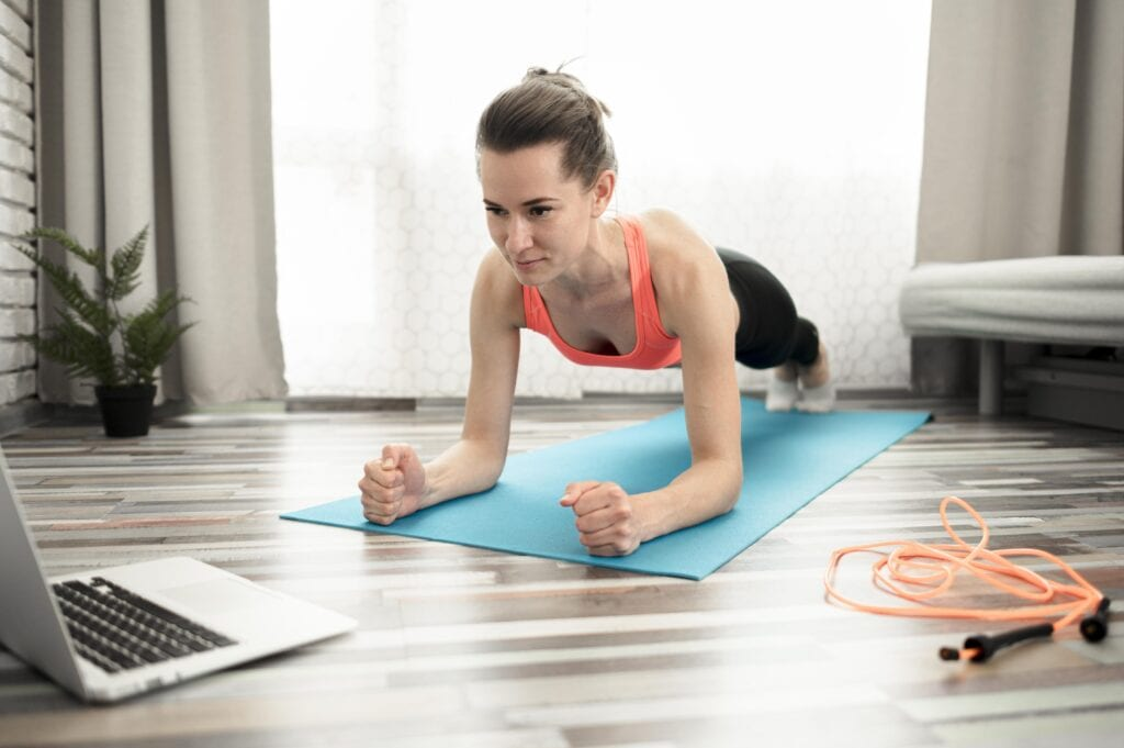 Strong woman doing online workout on mat with jump rope nearby