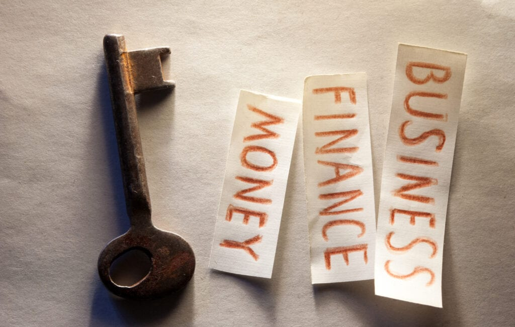 An iron key and three pieces of paper with words written on them
