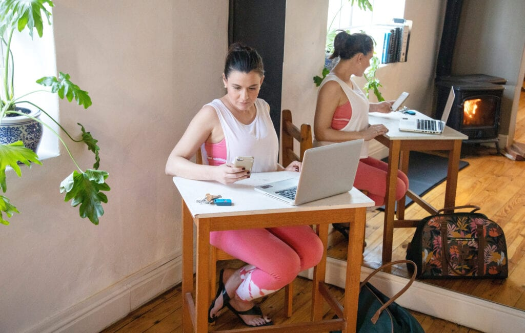 Busy female Pilates instructor working at her desk