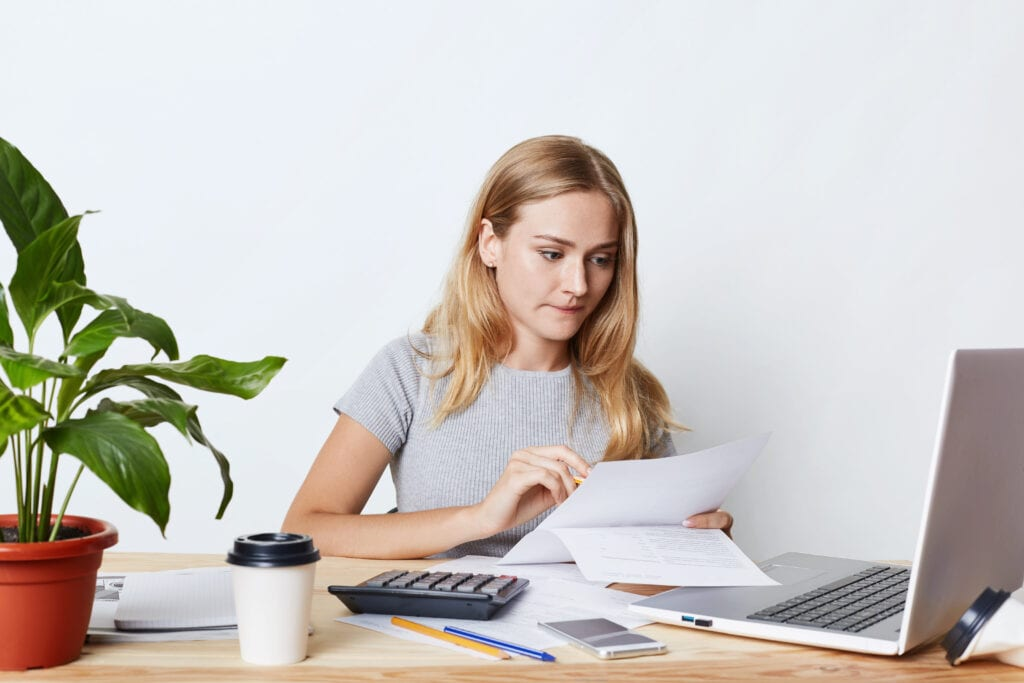 Woman at desk looking at papers computer screen and calculator