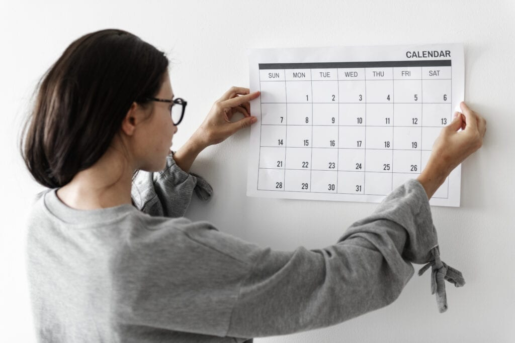 Woman wearing sweater and glasses pinning monthly calendar to the wall