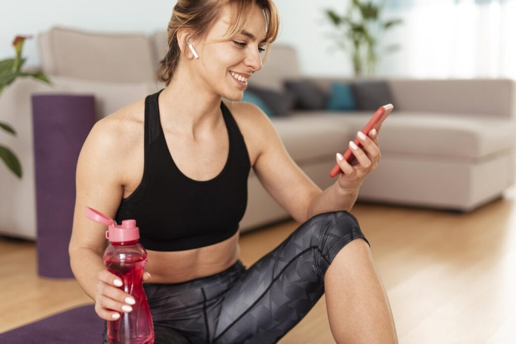 Fit woman looking at her phone