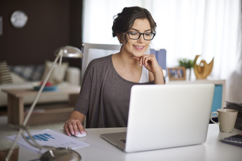 Woman smiling in home office working on computer