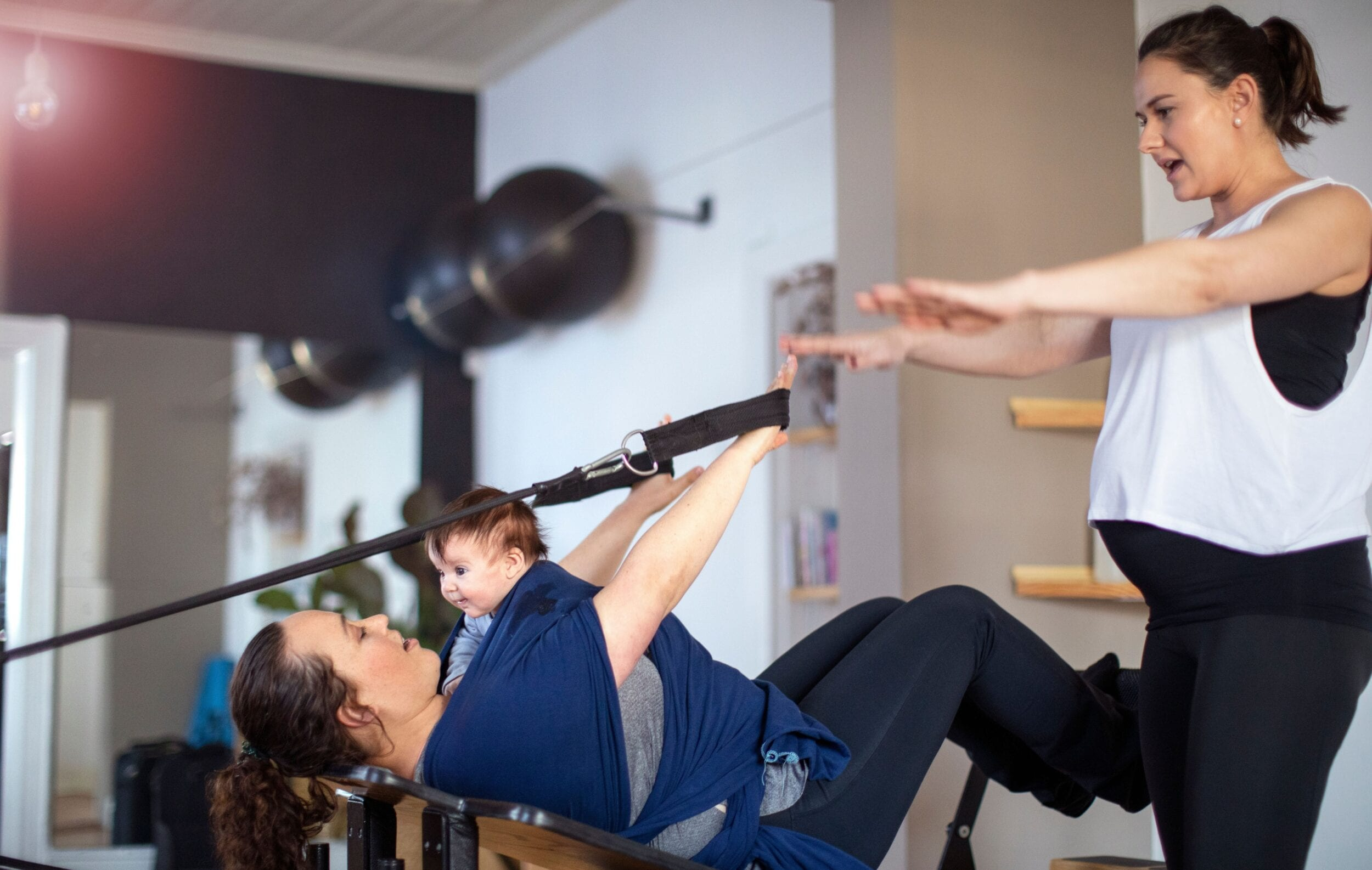 Pregnant Pilates teacher assisting her client while doing the Pilates exercise