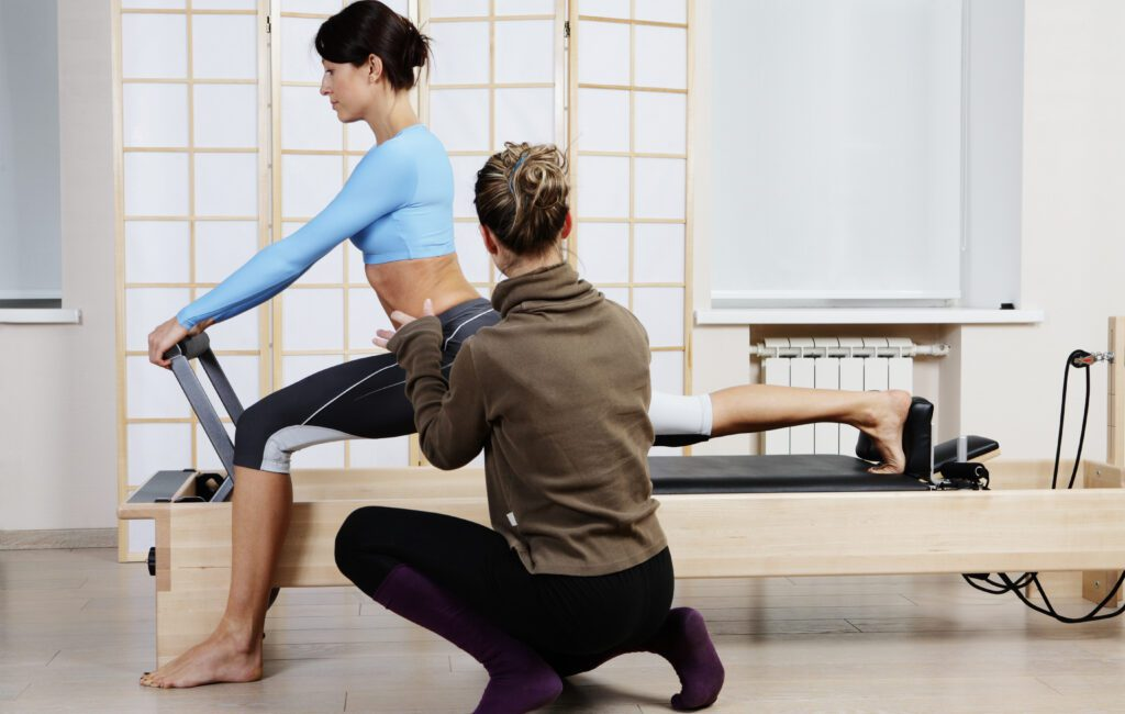 Pilates instructor helping her client during Pilates class