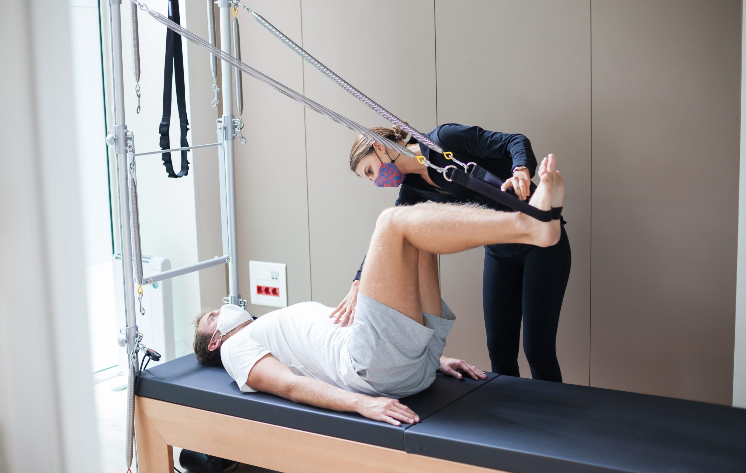 Pilates instructor assisting her client during Reformer workout while wearing masks