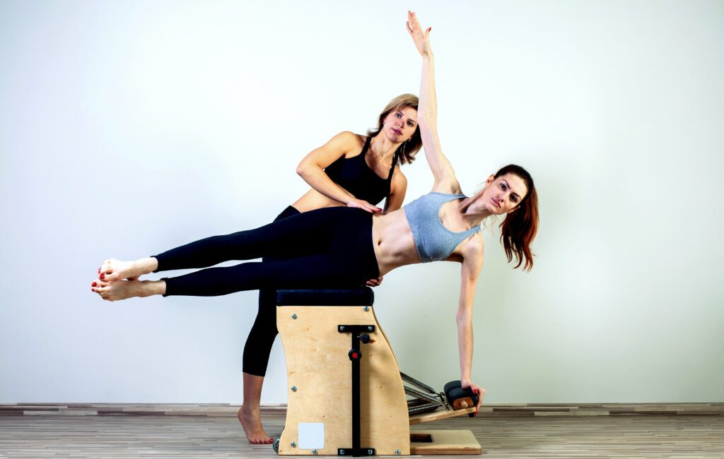 Pilates instructor helping her client while doing Wunda chair workout