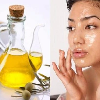Woman applying oil to her face
